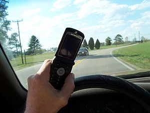 Young driver texting while driving.