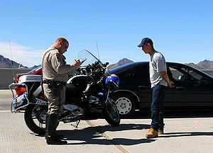 A motor officer writes a traffic ticket for a ...