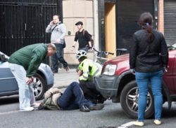 An automobile gets into an accident with a cyclist in New York City.