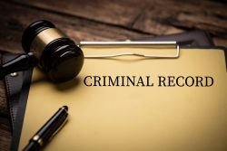 Criminal Record text on Document and gavel isolated on wooden office desk close up