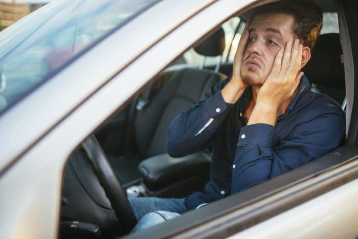 man is worried in car