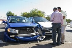 Two men conferring next to two smashed cars.